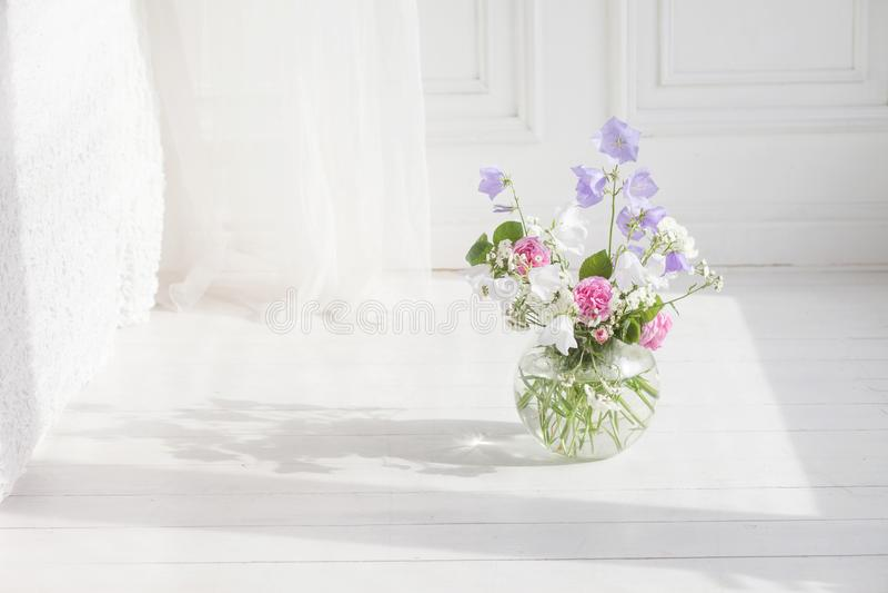 Το βάζο γυαλιού με την πασχαλιά, αυξήθηκε και άσπρα floweers στο ελαφρύ άνετο εσωτερικό κρεβατοκάμαρων Άσπρος τοίχος, κρεβάτι με  στοκ εικόνες