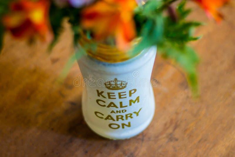 Το βάζο λουλουδιών με το κείμενο ` κρατά ήρεμος και συνεχίζει ` στοκ εικόνα