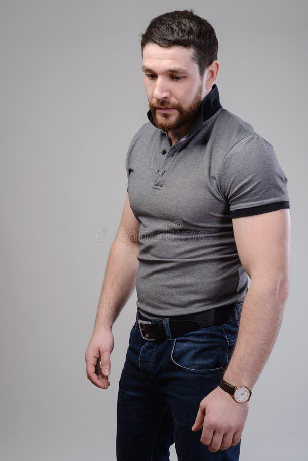 Το βάναυσο μυϊκό αρσενικό έντυσε σε μια μπλούζα πέρα από το γκρίζο υπόβαθρο στοκ εικόνα με δικαίωμα ελεύθερης χρήσης
