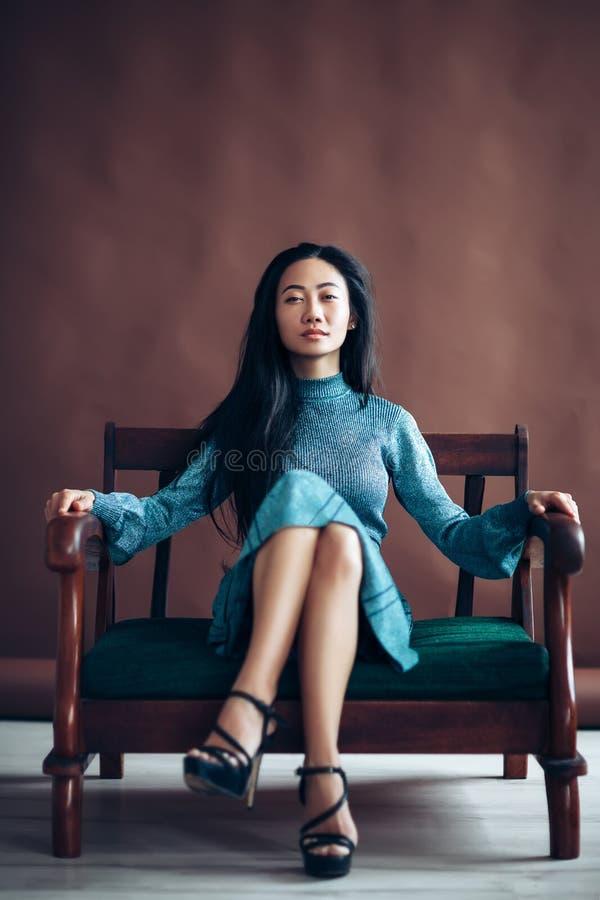 Το βέβαιο ασιατικό κορίτσι στο μπλε φόρεμα κάθεται στον καναπέ στοκ φωτογραφίες με δικαίωμα ελεύθερης χρήσης