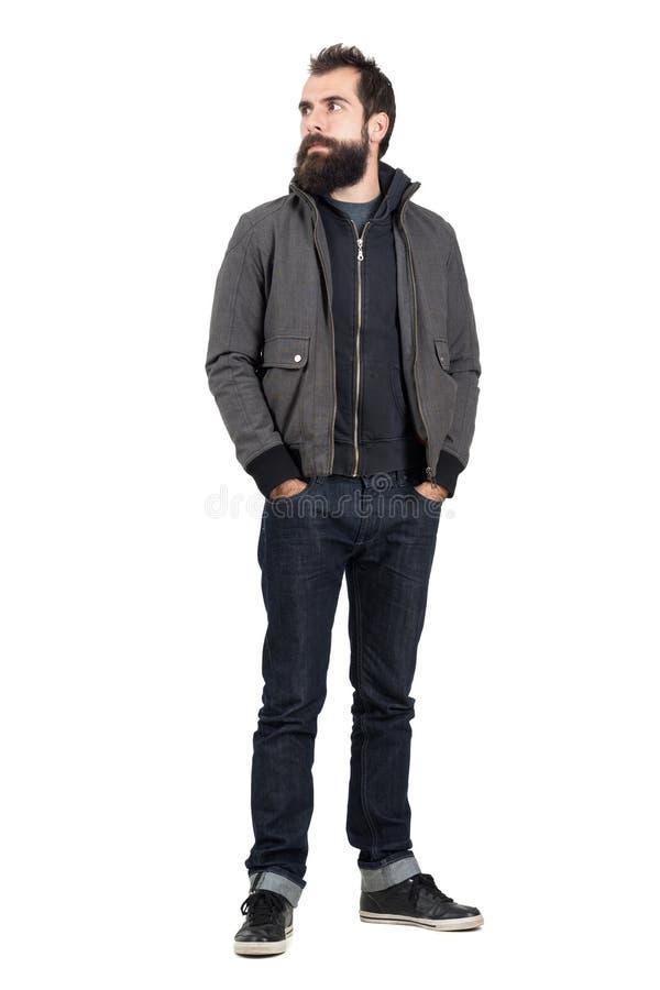Το βέβαιο μοντέρνο hipster που φορά το σακάκι πέρα από τη με κουκούλα μπλούζα που κοιτάζει μακριά με παραδίδει τις τσέπες στοκ φωτογραφία