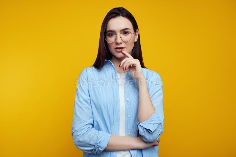 Το βέβαιο νέο κορίτσι κρατά το δάχτυλο κοντά στα χείλια, εξετάζοντας τη κάμερα, eyeglasses και το μπλε πουκάμισο, που απομονώνοντ στοκ εικόνα με δικαίωμα ελεύθερης χρήσης