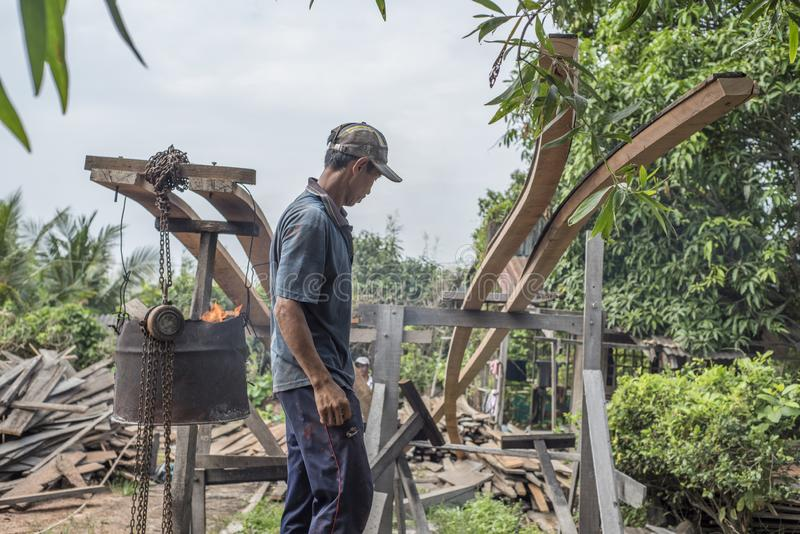 Το βιετναμέζικο άτομο εργάζεται στην κάμψη των μακριών σανίδων για τη βάρκα κάνοντας στον κόλπο Nga στο νότιο Βιετνάμ στοκ φωτογραφία με δικαίωμα ελεύθερης χρήσης