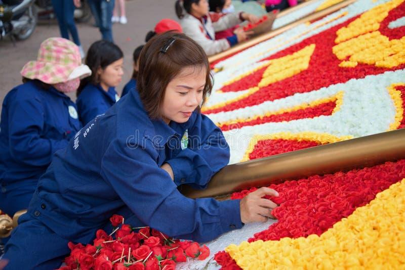 Το βιετναμέζικο κορίτσι βάζει μια εορταστική εγκατάσταση των τεχνητών λουλουδιών στοκ φωτογραφίες με δικαίωμα ελεύθερης χρήσης
