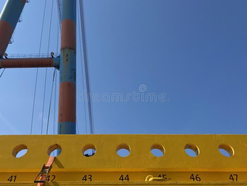 Το βιομηχανικό motiv με τις γιγαντιαίες κατασκευές γερανών και χάλυβα ένας βαθύς μπλε ουρανός με το αντίγραφο χωρίζει κατά διαστή στοκ εικόνα