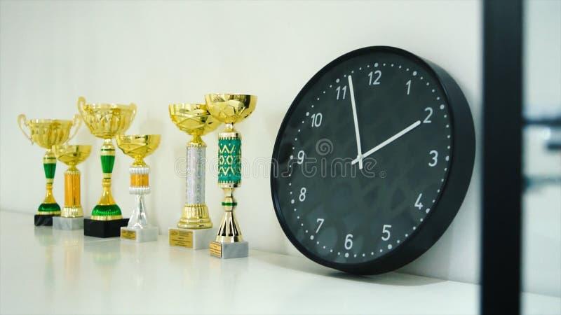 Το βραβείο τροπαίων για το νικητή παρουσιάζει στο ράφι απόθεμα Ρολόι και τρόπαια στο ράφι Η έννοια του χρόνου και του αθλητισμού στοκ εικόνες