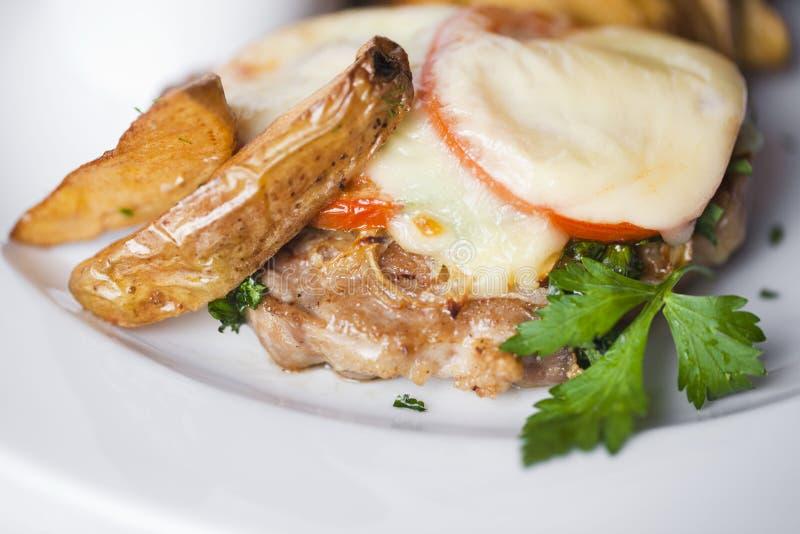 Το βόειο κρέας, χοιρινό κρέας, μοσχαρίσιο κρέας, έψησε το κρέας με τις ντομάτες και τη μαγιονέζα, σφήνες πατατών στη φλούδα σε έν στοκ φωτογραφίες