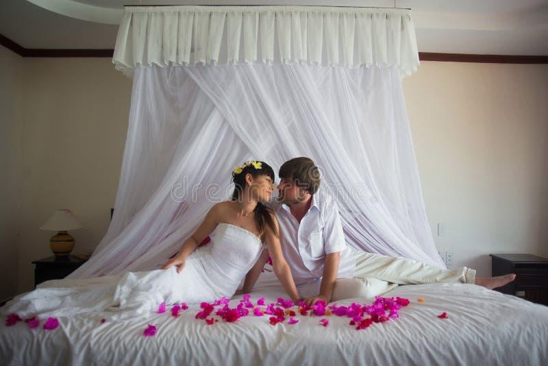 Το γαμήλιο ζεύγος κάθεται το ένα δίπλα στο άλλο, στηργμένος σε ένα κρεβάτι στοκ φωτογραφίες με δικαίωμα ελεύθερης χρήσης