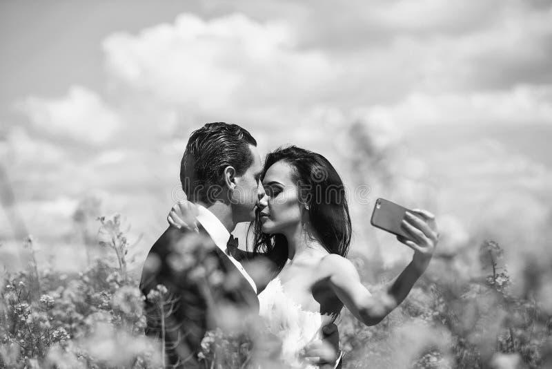 Το γαμήλιο ζεύγος κάνει selfie φιλί γαμήλιων ζευγών στα κίτρινα λουλούδια τομέων στοκ εικόνα