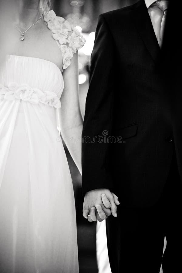 Το γαμήλιο ζεύγος κρατά τα χέρια τους στοκ φωτογραφία