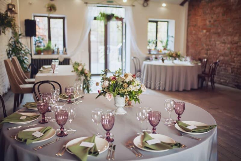Το γαμήλιο συμπόσιο, ύφος σοφιτών, εξυπηρέτησε τους πίνακες με τα λουλούδια και τα μέρη της πρασινάδας στοκ εικόνα