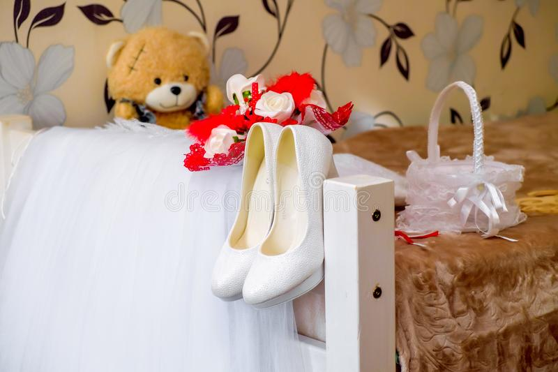 το γαμήλιο φόρεμα της νύφης με τα παπούτσια εξαρτημάτων αντέχει την ανθοδέσμη στοκ εικόνες με δικαίωμα ελεύθερης χρήσης