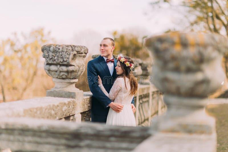 Το γαμήλιο πορτρέτο ευτυχούς μοντέρνου η νύφη και η τοποθέτηση νεόνυμφων στο παλαιό πεζούλι πετρών σταθμεύει την άνοιξη στοκ εικόνες
