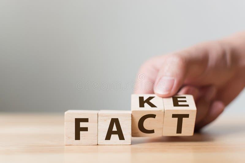 Το γεγονός ή η πλαστή έννοια, ξύλινος κύβος κτυπήματος χεριών αλλάζει τη λέξη, Απρίλιος στοκ φωτογραφία με δικαίωμα ελεύθερης χρήσης