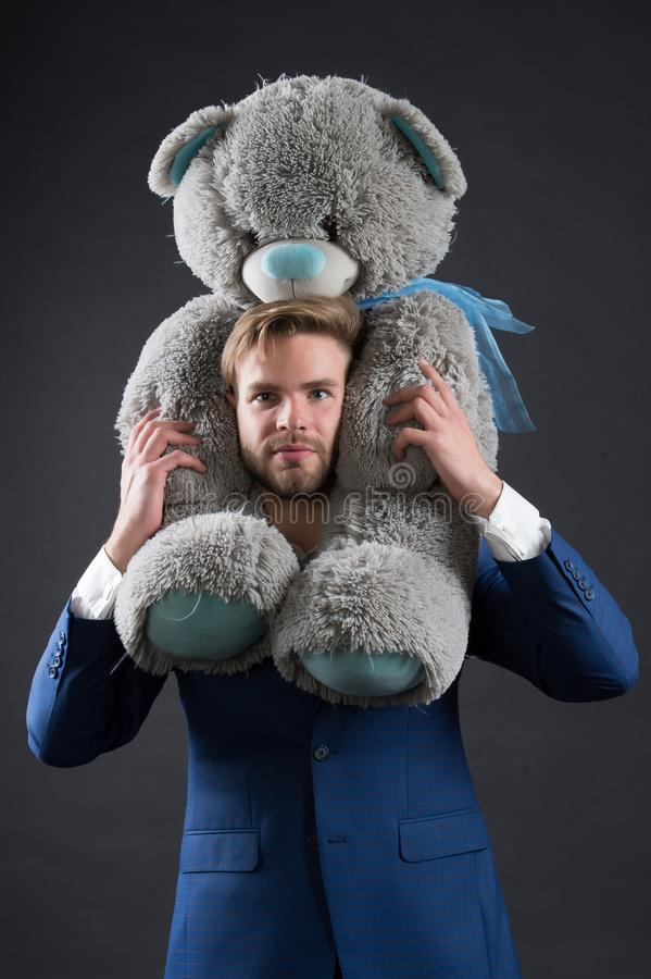 Το γενειοφόρο άτομο με γκρίζο teddy αντέχει Μεγάλο ζωικό παιχνίδι λαβής επιχειρηματιών Διευθυντής μόδας με το δώρο ή το παρόν παι στοκ φωτογραφία