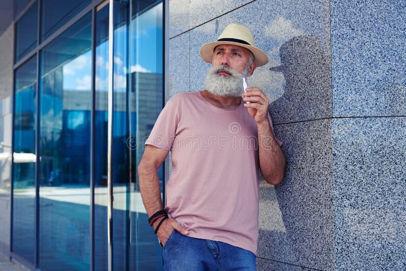 Το γενειοφόρο άτομο με το ηλεκτρο τσιγάρο κοίταξε σοβαρά στοκ φωτογραφίες