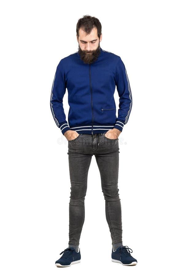 Το γενειοφόρο hipster στα αναδρομικά ενδύματα με παραδίδει τις τσέπες κοιτάζοντας κάτω στοκ φωτογραφία με δικαίωμα ελεύθερης χρήσης
