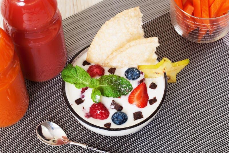 Το γιαούρτι με τα μούρα και τη σοκολάτα βακκινίων φραουλών μεντών σκορπίζει ακόμα τη ζωή, ραβδιά καρότων, μπουκάλια χυμού στοκ φωτογραφία με δικαίωμα ελεύθερης χρήσης