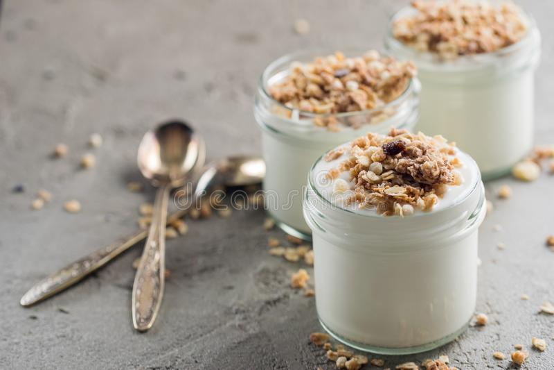 Το γιαούρτι με το granola φιαγμένο από βρώμες, σταφίδες, ξεφύσηξε το ρύζι, τη σοκολάτα και τις ξηρές μπανάνες Υγιές πρόγευμα για  στοκ φωτογραφία με δικαίωμα ελεύθερης χρήσης