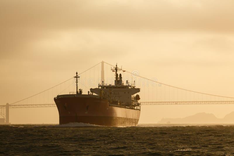 Το γιγαντιαίο σκάφος πετρελαιοφόρων γλιστρά κάτω από τη χρυσή γέφυρα πυλών στον τίτλο ηλιοβασιλέματος έξω στη θάλασσα στοκ εικόνα με δικαίωμα ελεύθερης χρήσης
