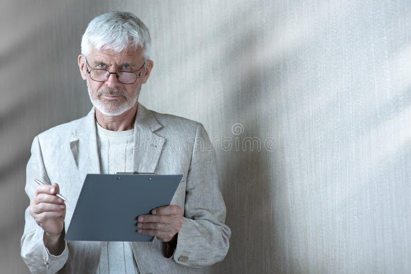 Το γκρίζος-μαλλιαρό άτομο στα ελαφριά ενδύματα και τα γυαλιά εισάγει σε μια σύμβαση σε χαρτί στοκ εικόνες
