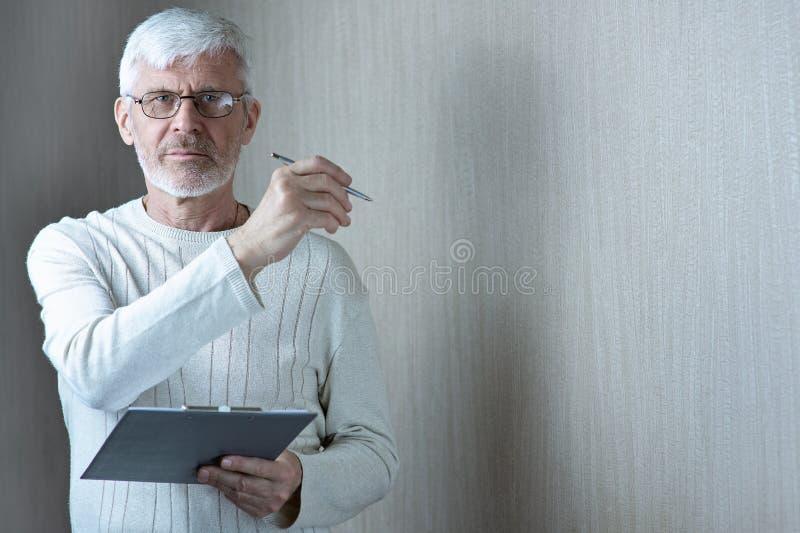 Το γκρίζος-μαλλιαρό άτομο στα ελαφριά ενδύματα και τα γυαλιά εισάγει σε μια σύμβαση σε χαρτί στοκ φωτογραφία με δικαίωμα ελεύθερης χρήσης