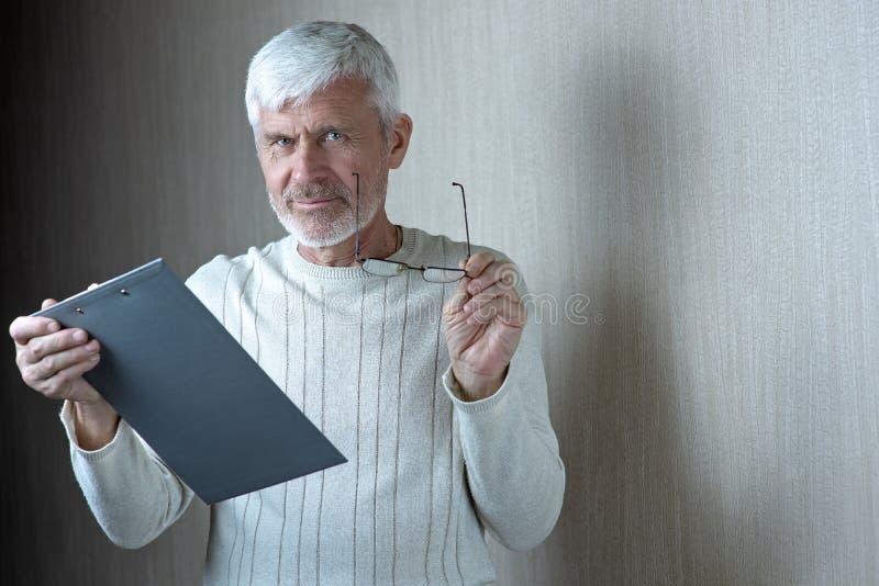 Το γκρίζος-μαλλιαρό άτομο στα ελαφριά ενδύματα και τα γυαλιά εισάγει σε μια σύμβαση σε χαρτί στοκ φωτογραφία