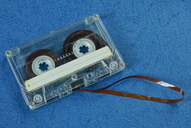 το γκρίζο παλαιό audiotape βρίσκεται στον μπλε πίνακα στοκ φωτογραφίες με δικαίωμα ελεύθερης χρήσης