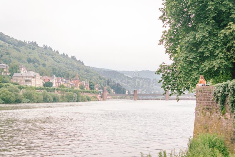 Το γλυκό ζεύγος κάθεται μαζί στο τουβλότοιχο στη Χαϋδελβέργη το πρωί πέρα από τον ποταμό του Ρήνου με το τοπίο φύσης στοκ φωτογραφίες με δικαίωμα ελεύθερης χρήσης