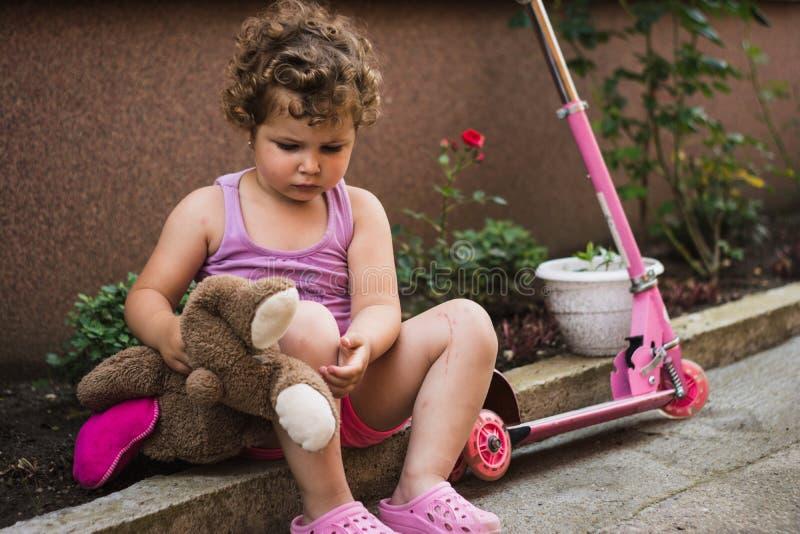 Το γλυκό μικρό κορίτσι με τη σγουρή τρίχα κάθεται και στηρίζεται κοντά στο ρόδινο μηχανικό δίκυκλό της στο προαύλιο στοκ εικόνες με δικαίωμα ελεύθερης χρήσης
