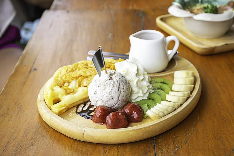 Το γλυκό νερό χύνει στη βάφλα με το παγωτό και τα φρούτα συμπεριλαμβανομένων των μπανανών, το ακτινίδιο και τις φράουλες στο ξύλι στοκ φωτογραφία