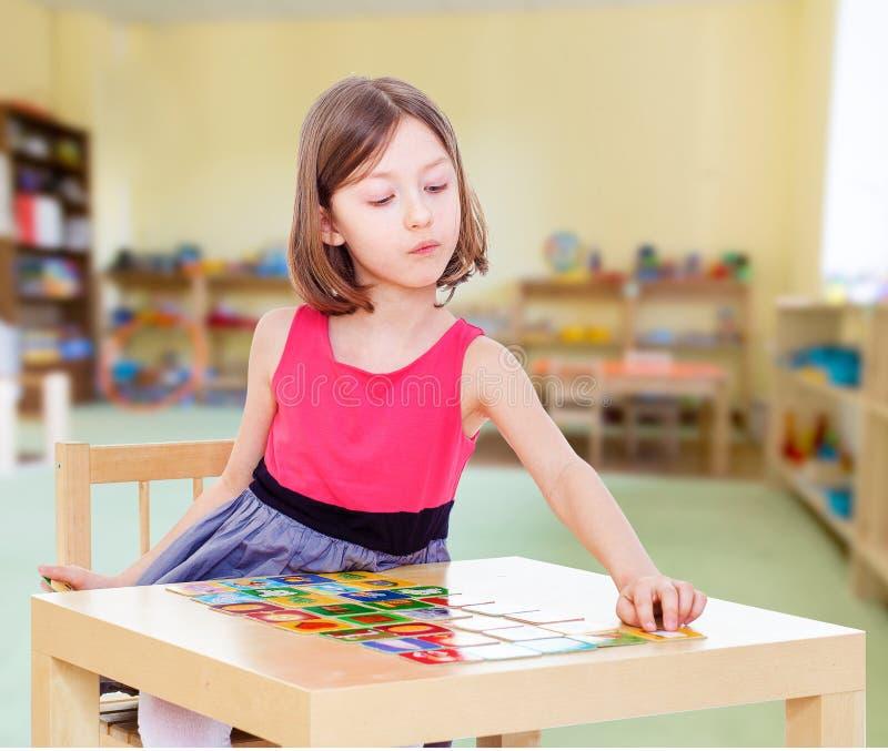 Το γοητευτικό κορίτσι κάθεται σε έναν πίνακα στοκ εικόνα