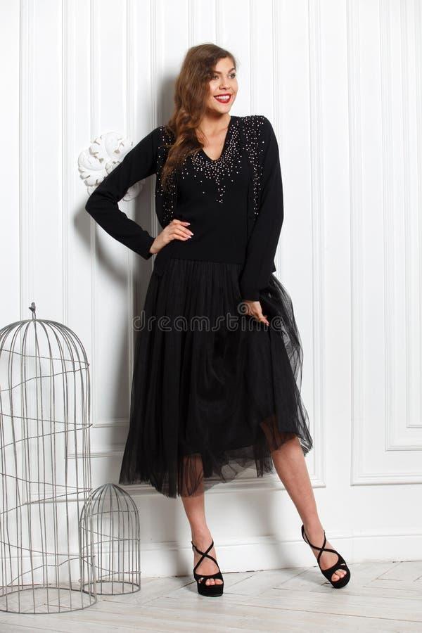 Το γοητευτικό κορίτσι που ντύνεται σε ένα μοντέρνο μαύρο πουλόβερ και μια μαύρη πλήρη φούστα θέτει ενάντια σε έναν άσπρο τοίχο στ στοκ εικόνα με δικαίωμα ελεύθερης χρήσης