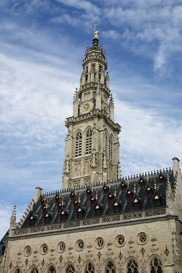 Το γοτθικό Δημαρχείο και ο πύργος καμπαναριών του στη γαλλική πόλη Arras σε έναν μπλε ουρανό με το άσπρο υπόβαθρο σύννεφων, παγκό στοκ εικόνα