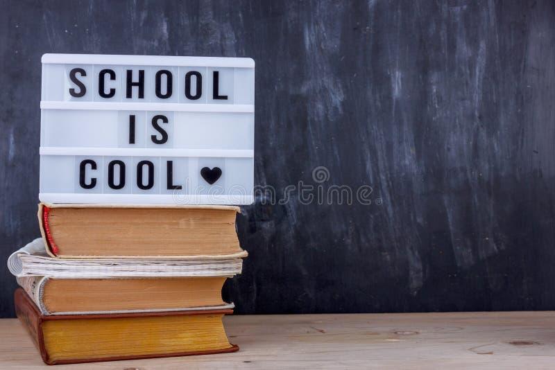 Το γράφοντας σχολείο έχει δροσιά σε έναν σωρό των βιβλίων Μαύρο γραφείο γραψίματος στο υπόβαθρο στοκ φωτογραφία με δικαίωμα ελεύθερης χρήσης
