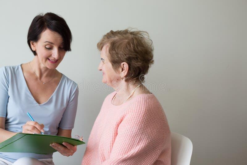Το γράψιμο γυναικών γιατρών απαντά κάτω στο ηλικιωμένο θηλυκό στοκ εικόνα με δικαίωμα ελεύθερης χρήσης