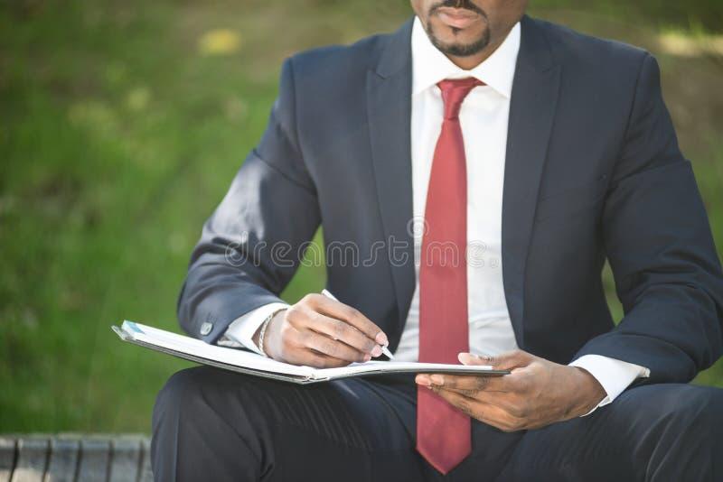 Το γράψιμο επιχειρηματιών σημειώνει καθμένος σε έναν πάγκο στοκ εικόνες