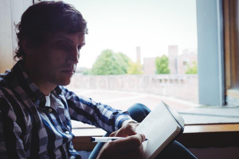 Το γράψιμο σπουδαστών σημειώνει κοντά στο παράθυρο στοκ φωτογραφία με δικαίωμα ελεύθερης χρήσης