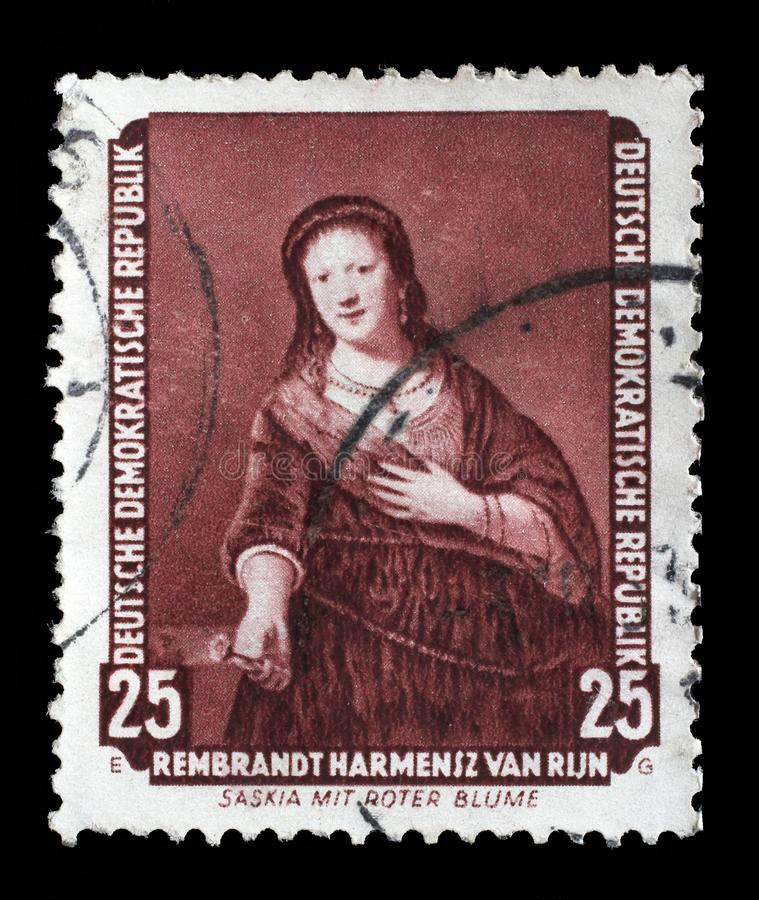 Το γραμματόσημο που τυπώνεται στην ΟΔΓ παρουσιάζει τη ζωγραφική Saskia με το κόκκινο λουλούδι, από Rembrandt στοκ εικόνα με δικαίωμα ελεύθερης χρήσης