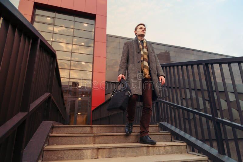 Το γραφείο έντυσε fashionably το νέο επιχειρησιακό άτομο με έναν χαρτοφύλακα που περπατά μέσω της πόλης στοκ φωτογραφίες με δικαίωμα ελεύθερης χρήσης