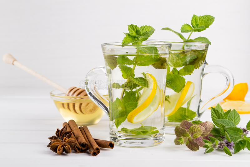 Το γυαλί δύο κοιλαίνει το φρέσκο τσάι μεντών με το λεμόνι και το μέλι στο άσπρο υπόβαθρο στοκ φωτογραφίες