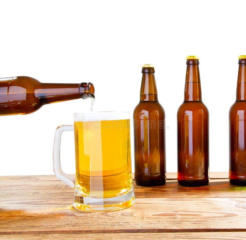 Το γυαλί και το μπουκάλι της μπύρας χωρίς τα λογότυπα στον ξύλινο πίνακα απομόνωσαν το διάστημα αντιγράφων, χλεύη μπουκαλιών επάν στοκ φωτογραφία
