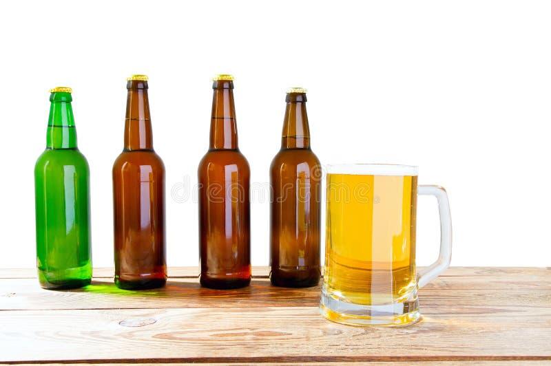 Το γυαλί και το μπουκάλι της μπύρας χωρίς τα λογότυπα στον ξύλινο πίνακα απομόνωσαν το διάστημα αντιγράφων, χλεύη μπουκαλιών επάν στοκ εικόνες