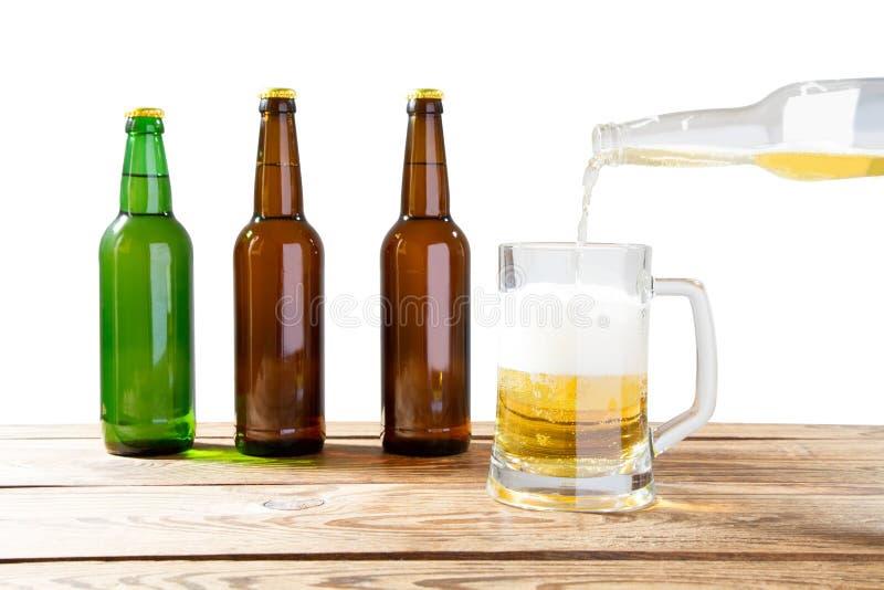 Το γυαλί και το μπουκάλι της μπύρας χωρίς τα λογότυπα στον ξύλινο πίνακα απομόνωσαν το διάστημα αντιγράφων, χλεύη μπουκαλιών επάν στοκ φωτογραφίες με δικαίωμα ελεύθερης χρήσης