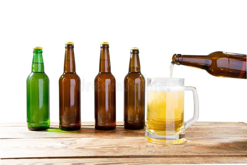 Το γυαλί και το μπουκάλι της μπύρας χωρίς τα λογότυπα στον ξύλινο πίνακα απομόνωσαν το διάστημα αντιγράφων, χλεύη μπουκαλιών επάν στοκ εικόνα
