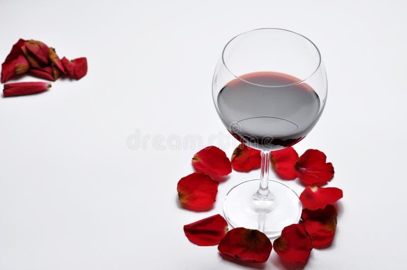 Το γυαλί κρασιού και όμορφος κόκκινος αυξήθηκαν απομονωμένος στο άσπρο υπόβαθρο τα πέταλα αυξήθηκαν r στοκ εικόνες με δικαίωμα ελεύθερης χρήσης