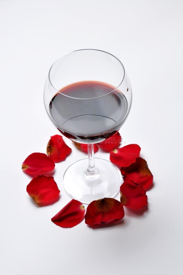Το γυαλί κρασιού και όμορφος κόκκινος αυξήθηκαν απομονωμένος στο άσπρο υπόβαθρο τα πέταλα αυξήθηκαν r στοκ εικόνα με δικαίωμα ελεύθερης χρήσης