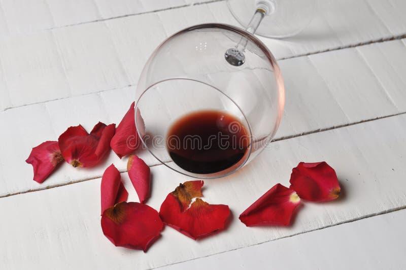Το γυαλί κρασιού και όμορφος κόκκινος αυξήθηκαν απομονωμένος στο άσπρο υπόβαθρο τα πέταλα αυξήθηκαν r στοκ εικόνες