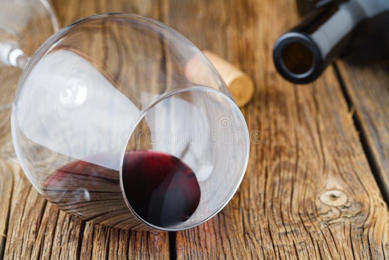 Το γυαλί κρασιού με την πτώση του κόκκινου κρασιού βάζει στον πίνακα στοκ εικόνες
