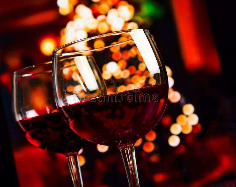 Το γυαλί κόκκινου κρασιού δύο ενάντια στα Χριστούγεννα ανάβει το υπόβαθρο διακοσμήσεων στοκ εικόνα με δικαίωμα ελεύθερης χρήσης